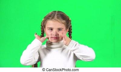 Child playing and make funny face on green screen at studio. Slow motion
