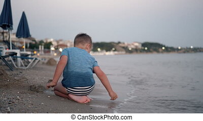 Child playing at the beach. Summer vacation