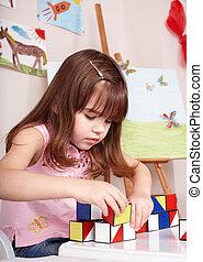 Child playing  block  in  preschool.