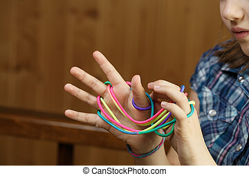 Child playing classic string game, creating shapes