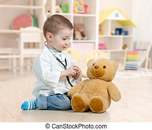 child playing doctor and curing plush toy indoors
