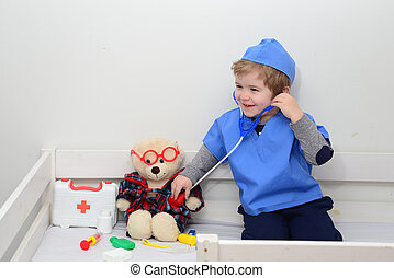 Child playing doctor or nurse with plush toy bear at home. Happy boy listens a stethoscope to toy. Playful boy child playing. Adorable child dressed as doctor playing with toy over white background.