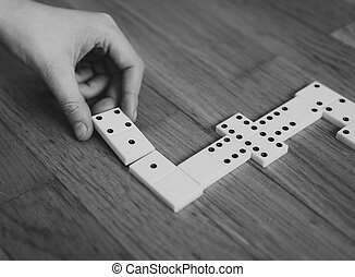 Child playing dominoes on the floor. Black and white.