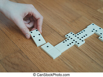 Child playing dominoes on the floor. Close-up view.