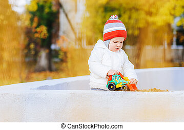 child playing excavator on the street