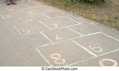 Child playing hopscotch at the kindergarten outdoors
