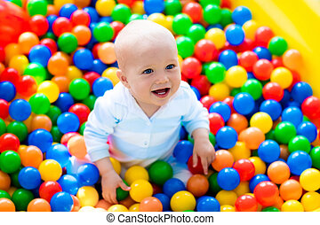 Child playing in ball pit on indoor playground - Happy...