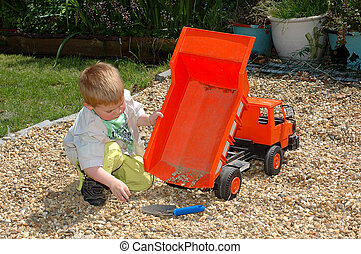 Child playing in garden. - Toddler playing with toy in ...