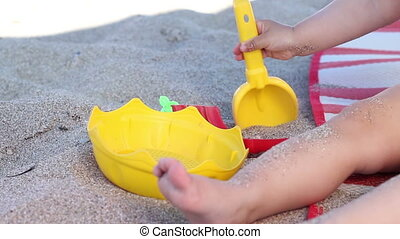 Child Playing in Sand - Baby is playing with shovel and pail...