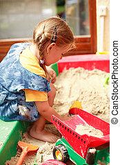 Child playing in sandbox - Little child playing in sandbox...