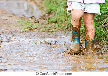 Child playing in the mud - Childs feet stomping in a mud...