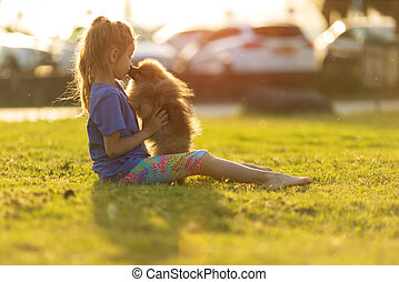 child playing in the park with pomeranian dog