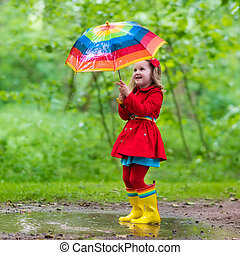 Little girl playing in rainy summer park. Child with colorful rainbow umbrella, waterproof coat and boots jumping in puddle in the rain. Kid walking in autumn shower. Outdoor fun by any weather