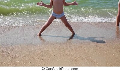 Child playing on a beach. Kid jumping in the waves. Sea vacation for family with kids. Little boy running on tropical beach of exotic island during summer holiday.