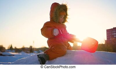 child playing on a snowy hill. Winter landscape. Sunset time
