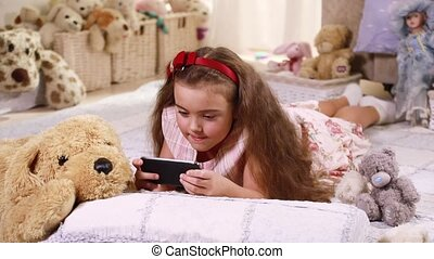 Child playing on a touch screen phone lying on the floor at...