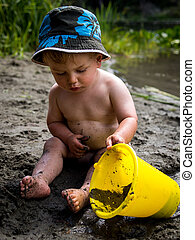 Child playing on beach with bucket
