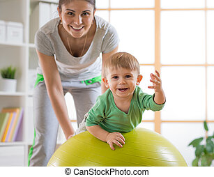 Child playing on gymnastic ball with mother at home