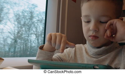 Child playing on touch pad during train ride - Boy traveling...