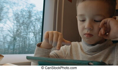 Child playing on touch pad during train ride
