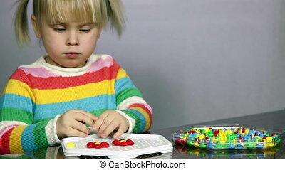 Cute three year old girl blond hair sitting at table playing puzzle game
