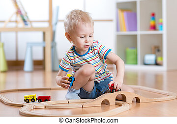 Child playing rail road toy in nursery