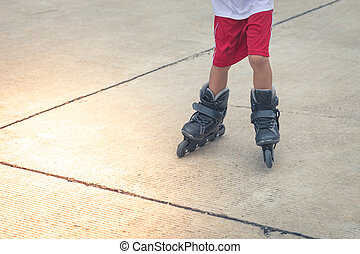 Child playing rollerblading in the Cement road