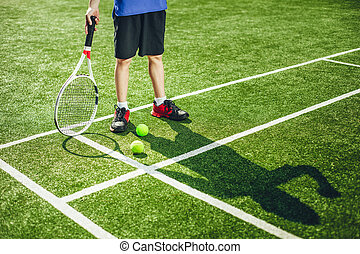 Child playing tennis on field