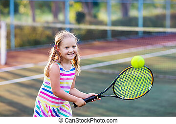 Child playing tennis on outdoor court. Little girl with...