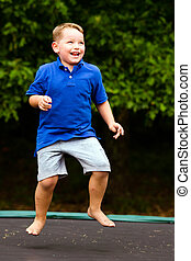 Child playing while jumping on trampoline