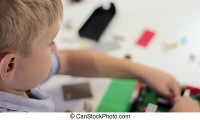 Child playing with a construction toy set. Copyspace