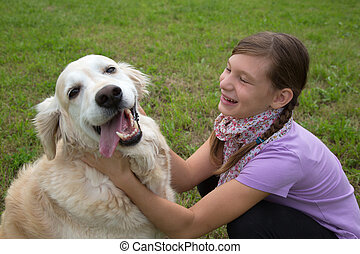 Child playing with a dog on a meadow