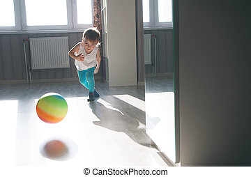 child playing with a multicolored ball in the apartment