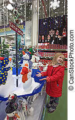 Child playing with artificial snow in store. Christmas decorations in the shop