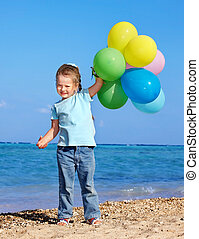 Child playing with balloons at the beach