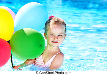 Child playing with balloons in swimming pool.