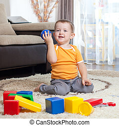 Child playing with building blocks at home.