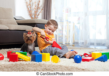 Child playing with building blocks at home. York dog sitting near boy.
