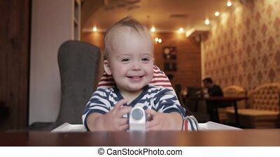 Child playing with car sitting in a high chair in a...