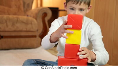 Child playing with colored blocks on floor in the room