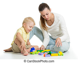 Child playing with colourful block toys on floor, isolated on white. Mother helps to son.