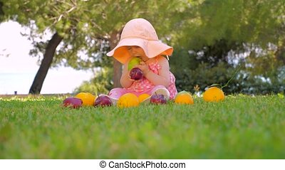 Child playing with fruits outdoor. Baby girl in panama ...