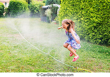 Child playing with garden sprinkler, jumping over