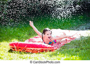Child playing with garden water slide - Little child playing...