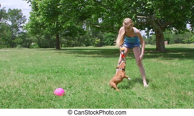 Child playing with her funny puppy dog on grass