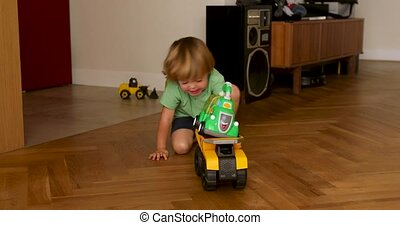 Child playing with machine on wooden floor - From above boy...