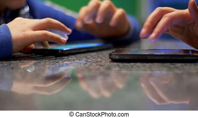 Child Playing with Phone Sitting at Table in a Cafe with People.