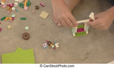 Child playing with plastic constructor. Toys on carpet...