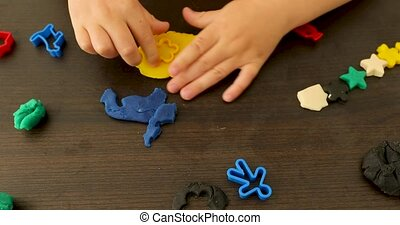 Child playing with plasticine - Crop hand of boy playing...