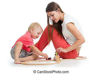 Child playing with railway toys on floor, isolated on white. Mother helps to son.